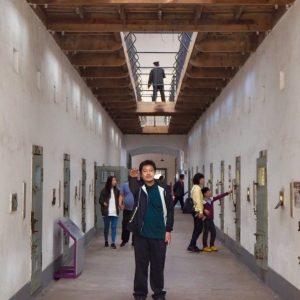 左右に独房が並ぶ廊下で敬礼する友人