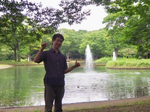 池の前に立つ筆者。後ろの噴水は高く上がっている。